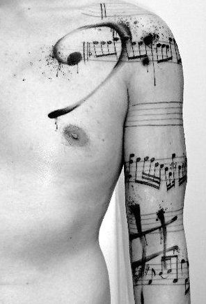 You see a lot of notes and music tattooed on people, but this one adds a nice messiness with the bass clef and sharp notation splattered over it.